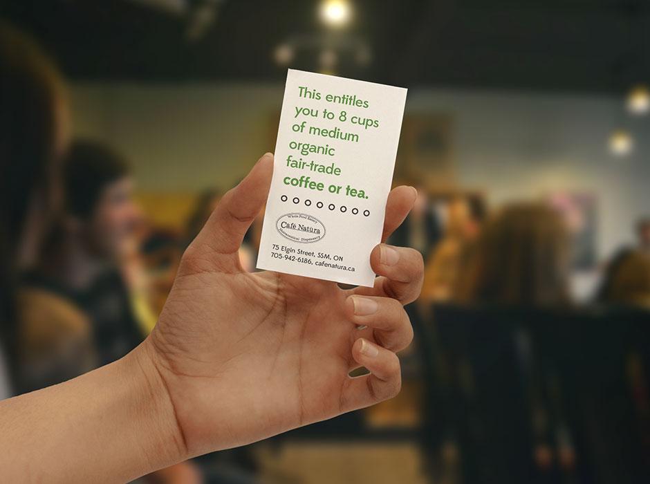 A person holding up a Café Natüra gift card.